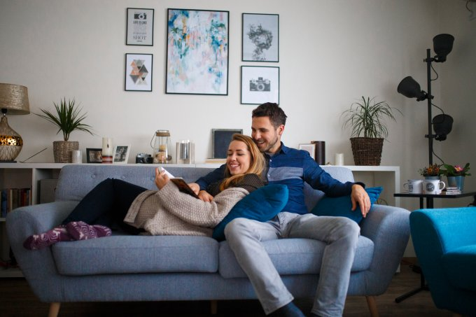 Young family couple together at home reading a book