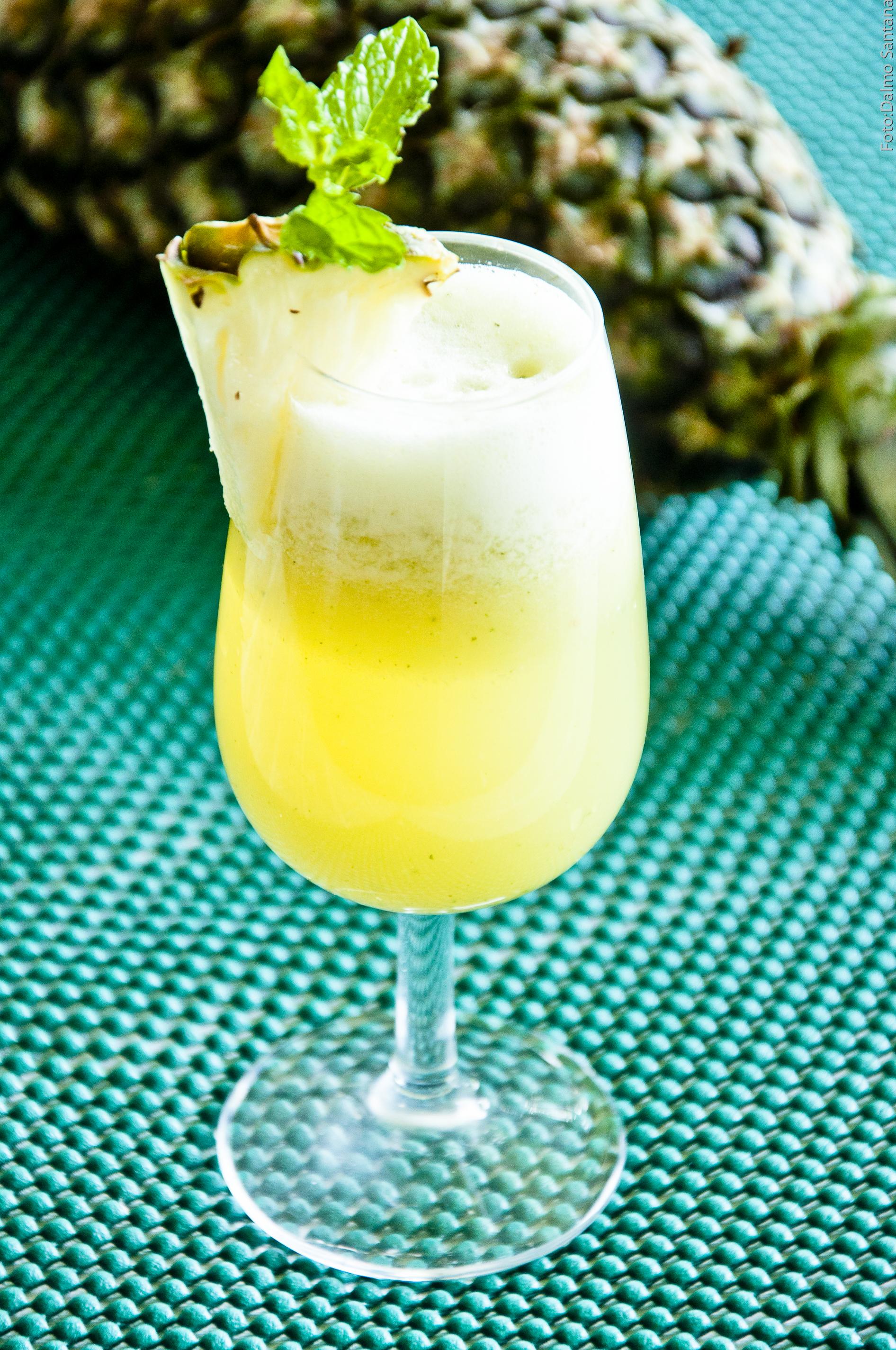 taça com suco de abacaxi e folhas de manjericão sobre uma toalha verde. Ao fundo, aparece um abacaxi inteiro