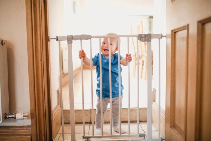 Bebê segurando grade de proteção