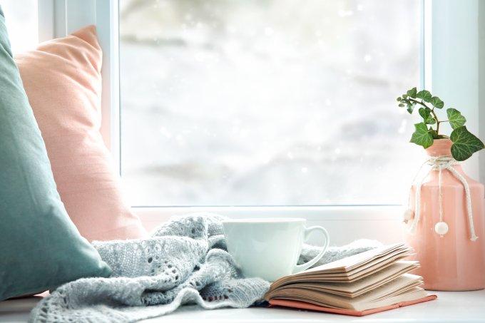 casa janela frio manta almofada xícara livro