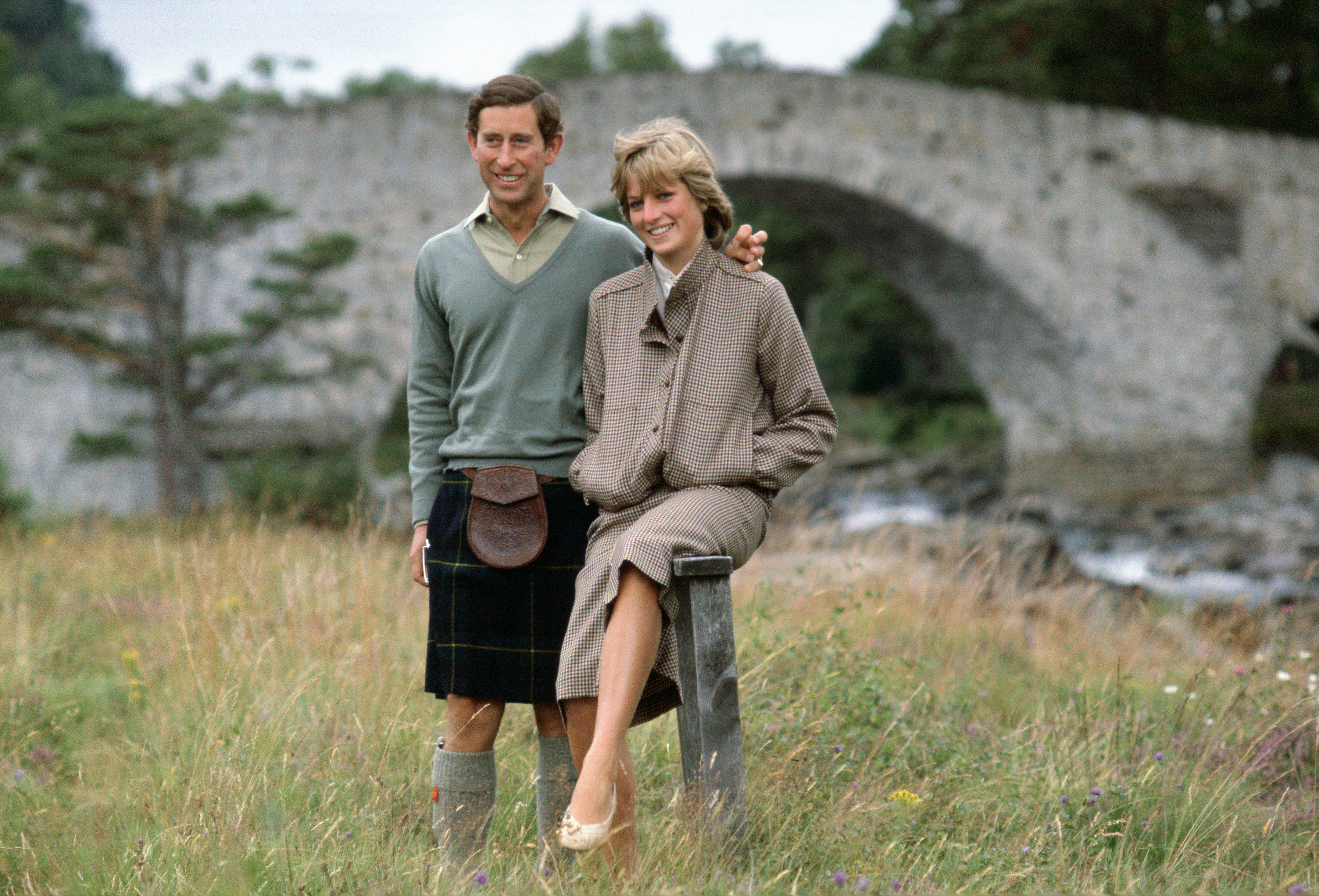 BALMORAL, UNITED KINGDOM - AUGUST 19: Prince Charles With His Arm Around His Wife, Princess Diana, During A Honeymoon Photocall By The River Dee. The Princess Is Wearing A Suit Designed By Bill Pashley With A Pair Of Shoes By The Chelsea Cobbler. The Prince Is Wearing A Kilt. (Photo by Tim Graham/Getty Images)