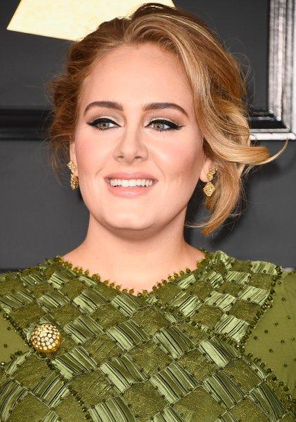 <strong>Adele:</strong> A grande vencedora da noite exibiu sua maquiagem favorita: delineado gatinho, esfumado iluminado e batom nude. Os cabelos foram presos em um coque clássico.