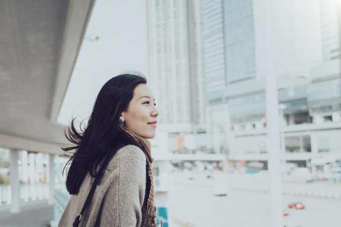 Beautiful young Asian lady overlooking cityscape of Hong Kong on urban bridge
