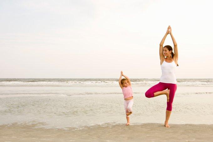 Mother teaches daughter yoga on beach