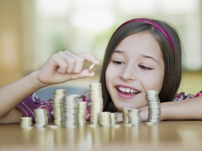 Garota colocando moedas em um cofrinho Chris Ryan