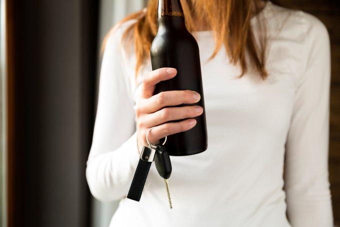 Mulher segurando bebida e chave do carro – Lei Seca