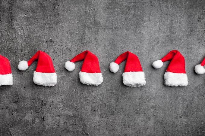 Gorros de Papai Noel vermelhos e enfileirados em fundo cinza