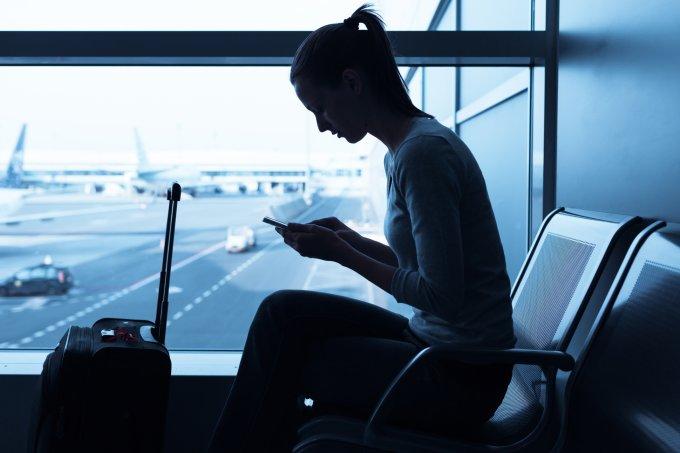 Mulher mexendo no celular no aeroporto