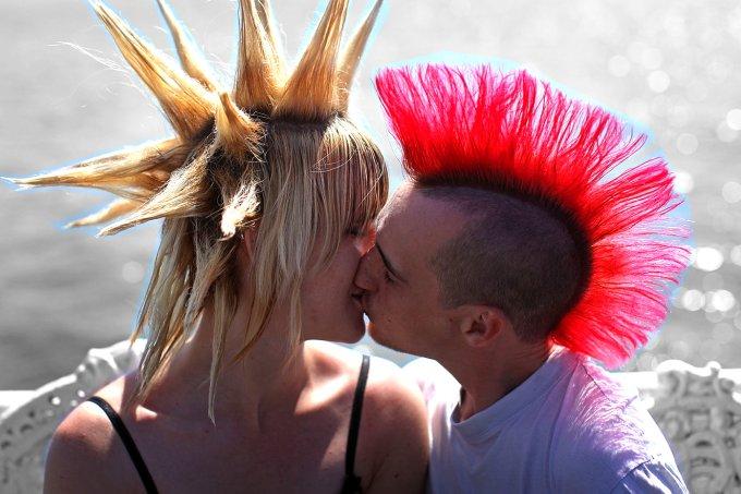 Casal de jovens punks se beijando durante festival na Inglaterra.