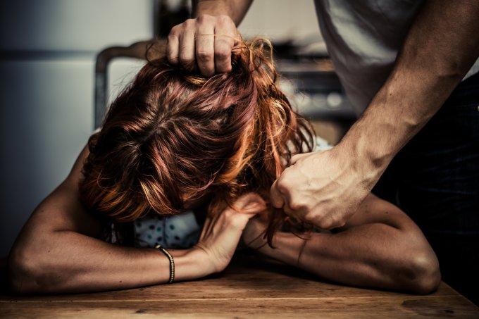 Homem puxando o cabelo de uma mulher ruiva, retratando um caso de violência física