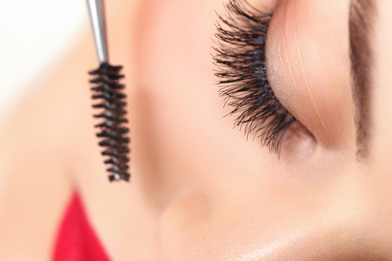 Olho feminino e aplicador de máscara para cílios