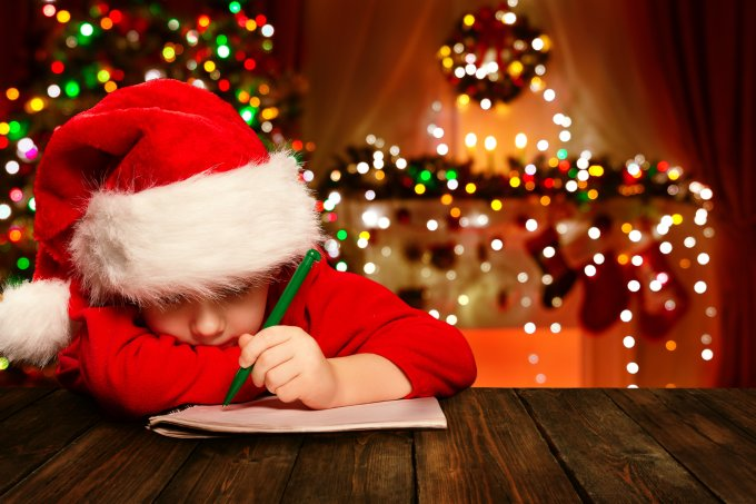 Criança com gorro de Papai Noel escrevendo carta