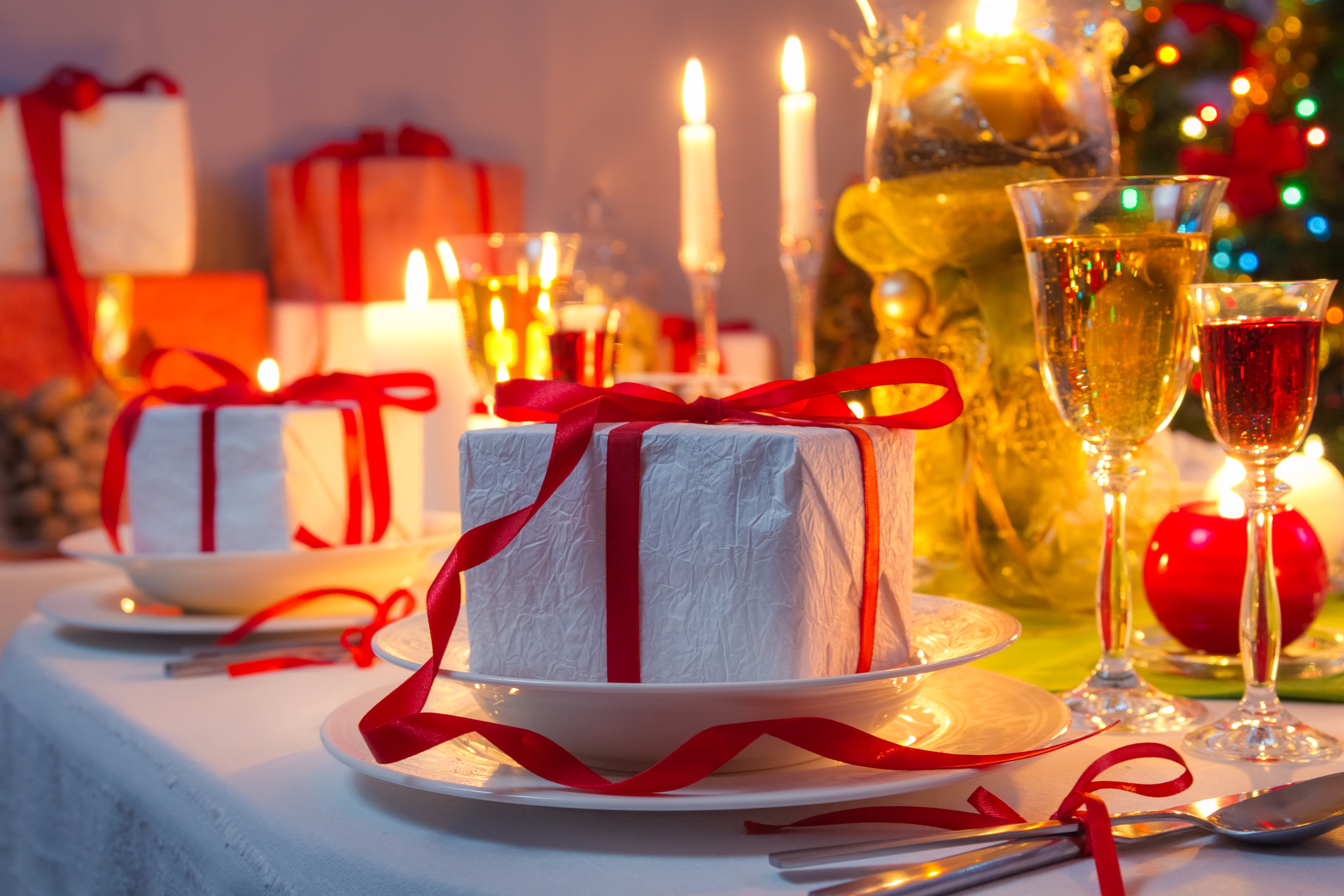 Mesa decorada para o Natal com lembrancinha posicionada sob os pratos