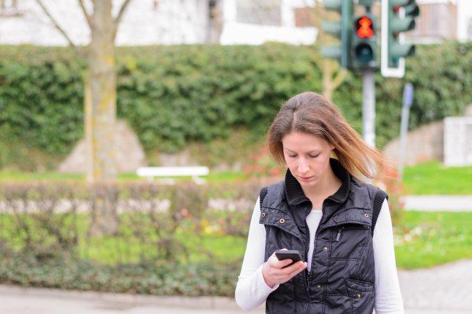 Mulher atravessa a rua enquanto olha o celular