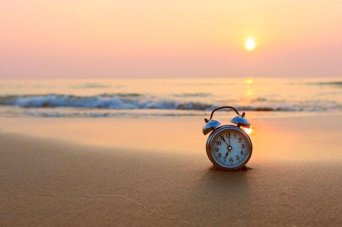 Relógio despertador na areia da praia