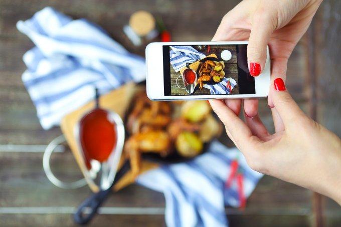 Mulher tirando fotos de comida para postar em seu Instagram