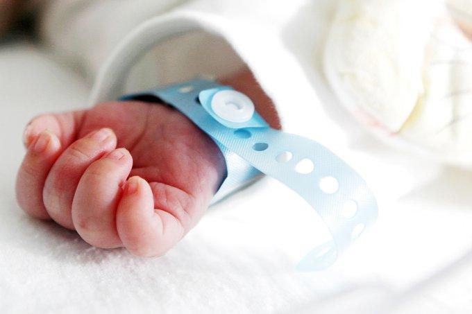 Mão de um recém-nascido com uma pulseira de identificação azul