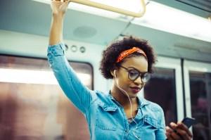 Mulher ouvindo música no metrô