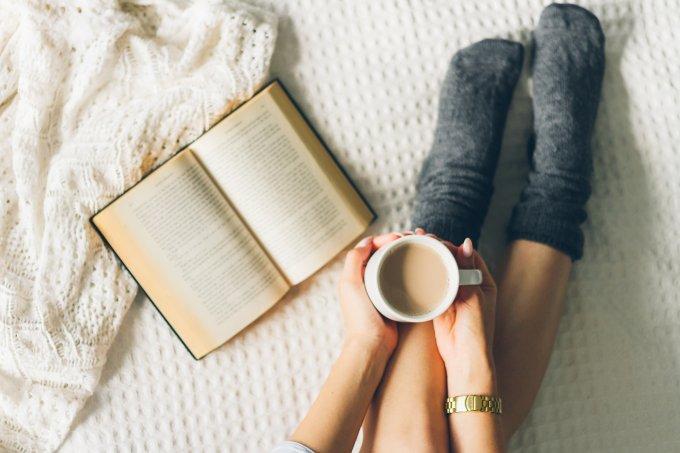 Mulher lendo livro e bebendo café com leite