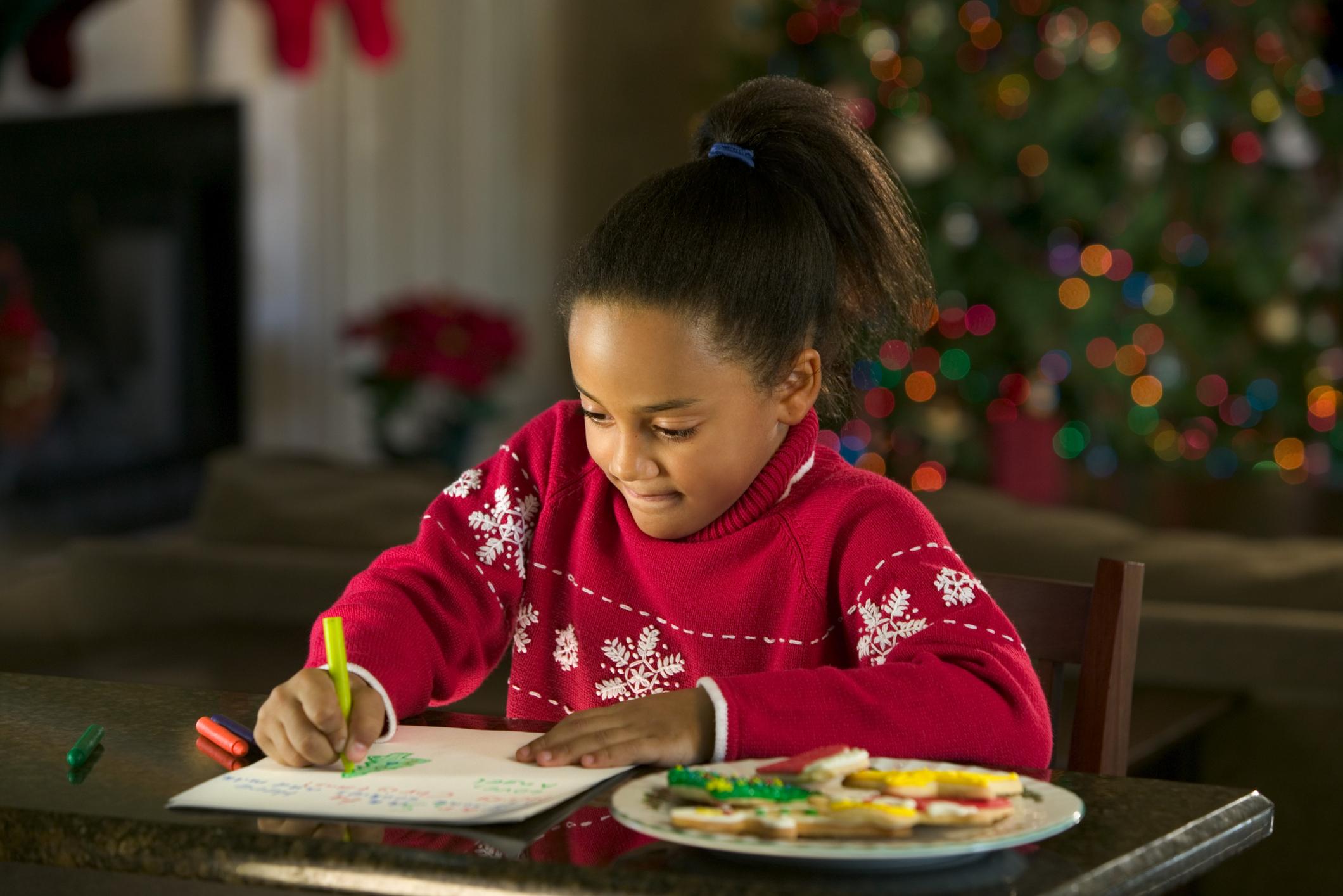 Garota de suéter vermelho escrevendo carta para Papai Noel