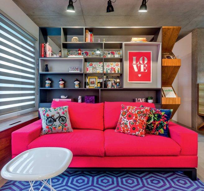 """Na sala projetada pela arquiteta Andrea Murao, sofá e tapete fazem uma parceria de peso. E, apesar de serem chamativos ao extremo, ambos conseguem a mesma dose de atenção. O segredo? """"O pink eleva a autoestima, faz vir à tona o melhor de nós. Já o azul é frio e acalma os ânimos. Juntos, trazem estabilidade"""", analisa Mon Liu, designer de interiores e especialista em cores, de São Paulo. As almofadas reúnem os tons da paleta. """"Para compensar tantos elementos que roubam a cena, a madeira e o branco promovem calma e paz"""", conclui."""