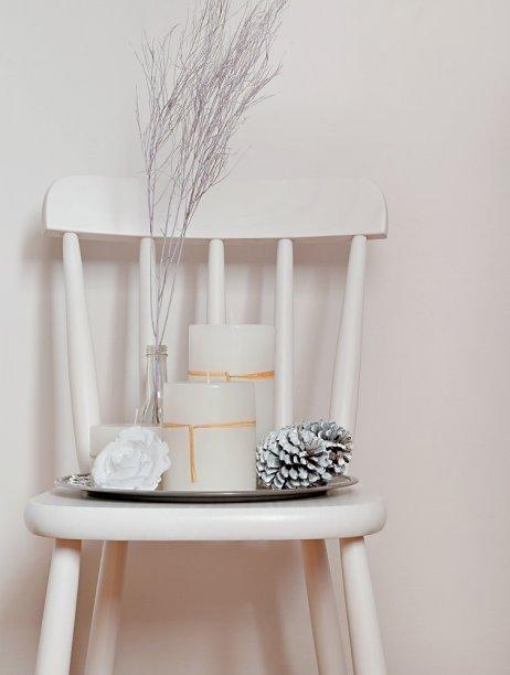 Até uma cadeira branquinha inspira um arranjo de provocar suspiros: objetos de mesma cor sobre uma bandeja. Peças customizadas acompanham velas de diferentes tamanhos. Um galho seco tingido de lilás - único item que escapa do tom predominante - tem como suporte uma velha garrafa de molho de pimenta. Já as pinhas do Natal passado receberam uma demão de tinta spray branca. Para finalizar, um botão de rosa artificial.