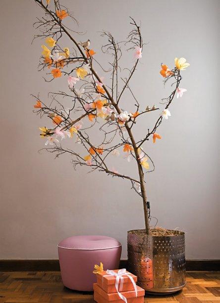 """O galho seco virou árvore de Natal com auxilio de flores de papel crepom presas nas luzinhas do pisca-pisca. Para recriar: corte o rolo de crepom a cada 6 cm. Arredonde uma das pontas de cada pedaço, abra a tira e cortes de seis em seis """"pétalas"""". Enrole em cada lâmpada, fixando com cola branca. Surpresa maior é o cachepô - um cesto de lavadora de roupa."""
