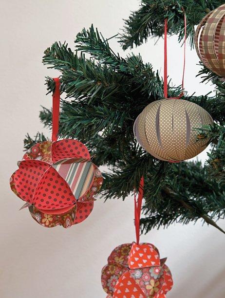 É possível poupar gastos na montagem da árvore e mesmo assim deixá-la exuberante. Uma dobradura com duas folhas de papel para scrapbook se torna uma exótica bola de origami, famosa técnica japonesa.