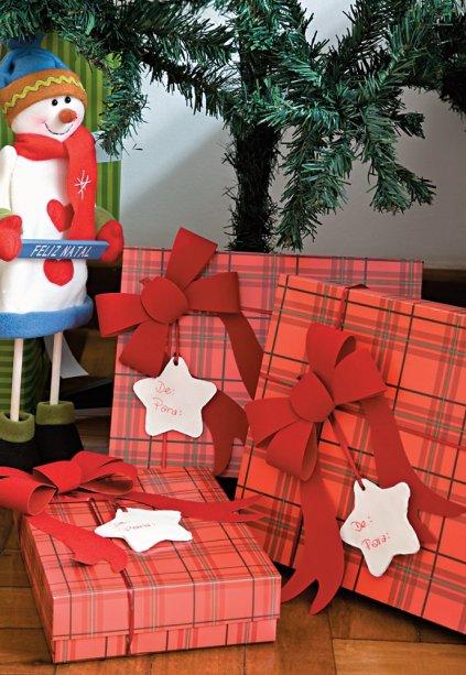 """Sob a supervisão do boneco de neve, as caixas de presente trazem um inusitado cartão """"de/para:"""" as estrelinhas são de biscuit cortado com forminha de biscoito. Depois, é só escrever com canetinha."""