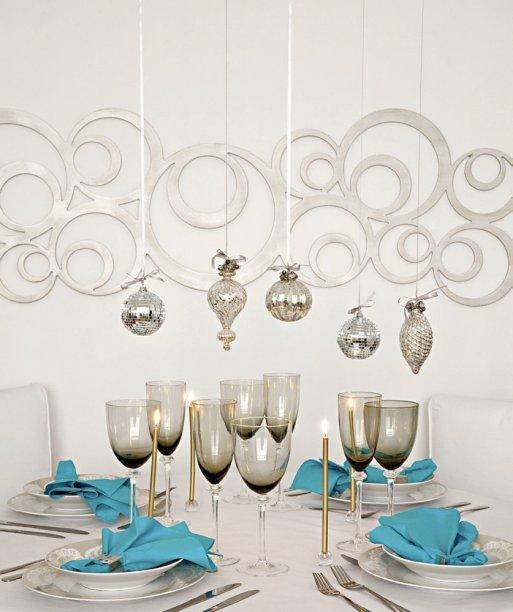No jantar, um modo de conquistar a atenção dos convidados é com um arranjo suspenso. Presas no teto com massa adesiva, Pritt Multi-tak, da Henkel, fitas fininha exibem gotas de vidro e bolas espelhadas. Surpreenda tembém com a paleta de cores: turquesa e dourado sobre o branco puro.