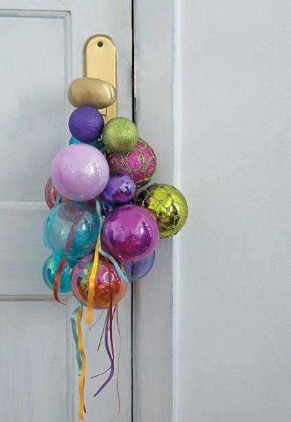 A porta de entrada também se veste de modo especial para a celebração. Pendurado na maçaneta, um cacho de diversas bolas amarradas com fitas de cetim dá as boas-vindas. A graça está em mesclar tamanhos, cores e texturas.