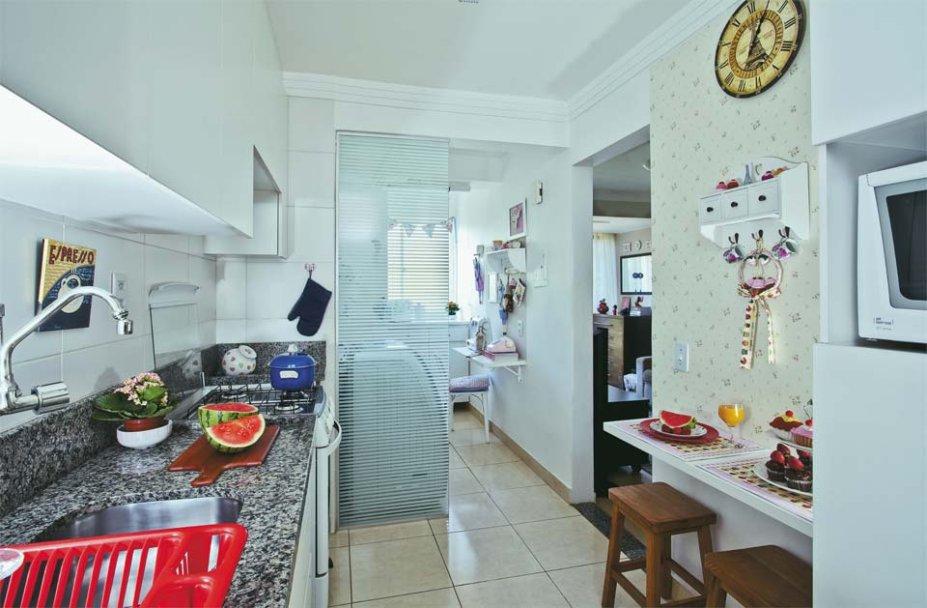 O cantinho de refeições da blogueira Ruby Fernandes é todo meigo com um papel de de parede com minirossas. Uma divisória de vidro separa a cozinha da área de serviço. Com uma película adesiva listrada, disfarça o ambiente, mas deixa entrar luz natural.