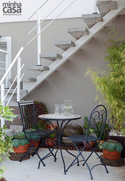 """No apartamento de cobertura da arquiteta Josanda Ferreira, de São Paulo, o acesso ao solário tornou-se um jardim zen. Sob a escada, deques amparam a fonte de arenito e o vaso com bambu. """"De acordo com o feng shui, esse conjunto traz prosperidade"""", conta a moradora. Bolachas de troncos de árvore (Shopping Garden) apoiam suculentas em cachepôs. As cadeiras e a mesa de ferro com tampo de mosaico são da Leroy Merlin."""