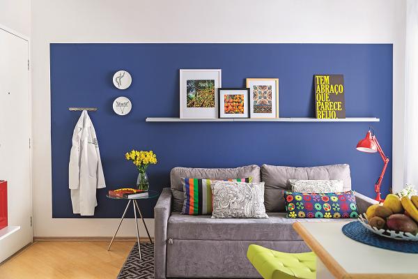 """<span>A estrela da sala é a parede azul (cor Tratamento Real, Coral) – note que ela não é inteiramente tingida, funcionando como um painel pintado. Neto dá as dicas para copiar: """"A referência para a altura deve ser a porta ou uma viga, o que estiver mais visível para equilibrar o alinhamento. Já para as laterais e a parte de baixo, sugiro afastamento de 15 a 20 cm"""". A proposta valoriza a superfície sem deixar o ambiente pesado. """"Uma saída para quem tem medo de abusar do tom escuro"""", apontao arquiteto Neto Porpino.</span>"""
