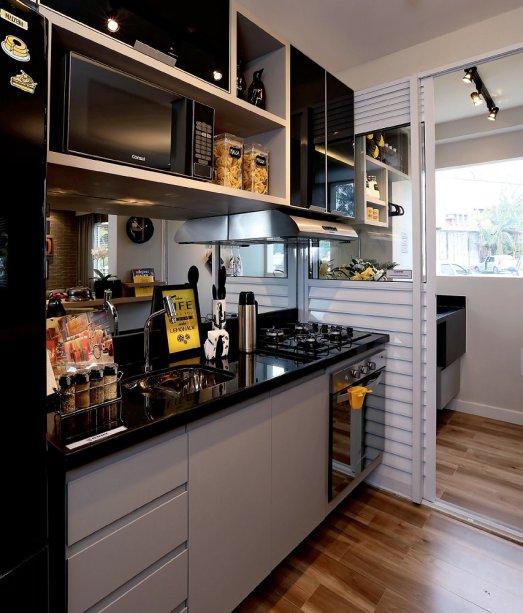 <span>Presença forte, o preto aparece nos móveis, na geladeira e até mesmo na iluminação, e é suavizado pelo uso da madeira. O porcelanato que imita o material natural (Grápia Rústico,da Itagres, Leroy Merlin) cobre o piso de todo apê (exceto o do banheiro). Projeto da arquiteta Carolina Ouro.</span>