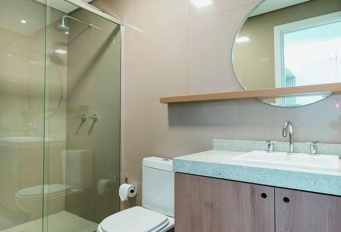 Apartamento pequeno com cores neutras e acabamentos amadeirados banheiros