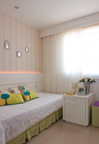 <span>As listras verticais do delicado papel de parede contrastam com as faixas horizontais do painel e do cortineiro. Sobre a cama, almofadas com estampas fofas acompanham as cores da decoração.</span>