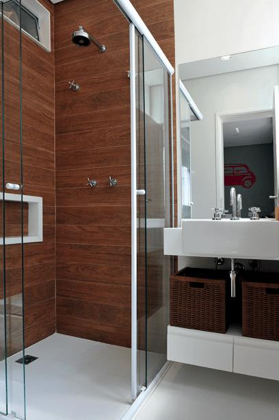 """<p style=""""text-align:justify;"""">º Menos banheiro, mais sala de banho. Guiada por essa ideia, a arquiteta Karina Korn trouxe para a área de banho o visual quente da madeira, na forma do porcelanato esmaltado Ipê HD, de 0,20 x 1,20 m, da Portinari (Leroy Merlin, R$ 137,90 o m²). No setor da bancada, prevalece o branco da marcenaria, da cuba de semiencaixe, do tampo de mármore e do piso de porcelanato Aspen Blanco Mate, 60 x 60 cm, da Roca.</p>"""