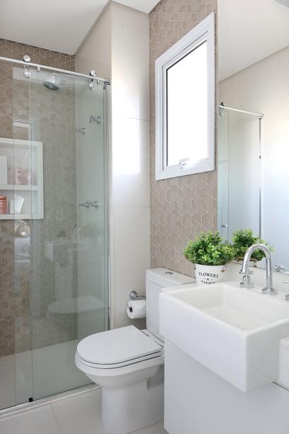 """<p style=""""text-align:justify;"""">º Como personalizar um banheiro de 2,80 m² novo e branquinho? A resposta dos arquitetos do Oficina 11.11 foi substituir parte do porcelanato Diamante Flash Polido (60 x 60 cm, da Portinari) das paredes por um mosaico de vidro com efeito 3D, o Box Beige, da Porto Design (Suriel Revestimento, R$ 1 154 a caixa com 1,40 m²). A área do chuveiro ganhou, ainda, um nicho de quartzo branco e um boxe com roldanas aparentes.</p>"""