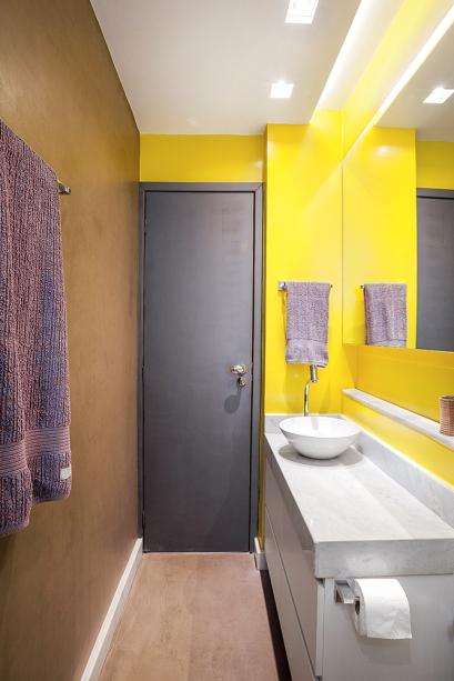"""<p style=""""text-align:justify;"""">º No banheiro estreito (1,16 x 2,72 m), a bancada mede 0,42 x 1 m (gabinete da Studio Movelaria, R$ 1 760). """"A torneira fica na lateral da cuba, descentralizada para melhor aproveitar a área"""", diz a arquiteta Natália Botelho, do Botti Arquitetura. Os acabamentos fogem do padrão: tinta Novacor Epóxi Amarelo Base DºÁgua, da Sherwin-Williams; esmalte no tom Ágata da Islândia, da Coral, na porta; e cimento queimado no piso e em outra parede.</p>"""