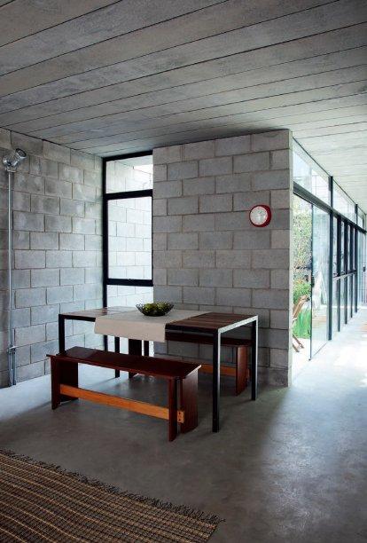 Na sala, os móveis de madeira aquecem o visual e se contrapõem ao cinza.