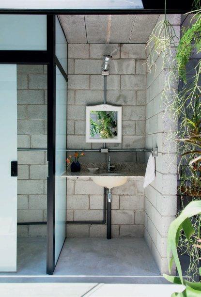 Um boxe de vidro cerca a área reservada do lavabo.