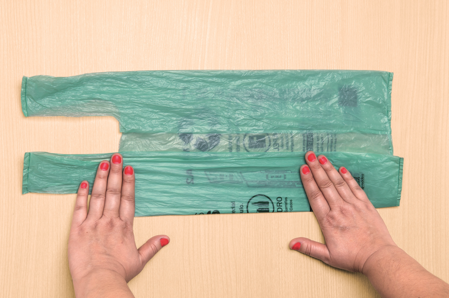 2. De baixo para cima, você irá dobrar a sacola três vezes: calcule aproximadamente a medida necessária para chegar a esse resultado e faça a primeira dobra. Alise o plástico.