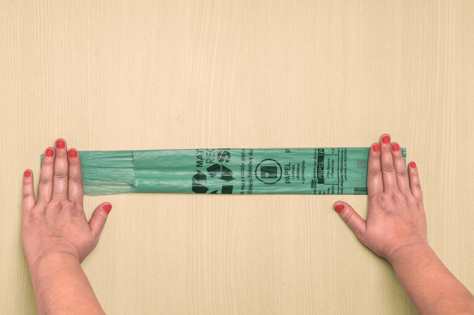 4. Ao fazer a última dobra, o formato fica parecido com o da foto - repare que as alças estão sobrepostas. Remova o ar do interior passando a mão da direita (base) para a esquerda (alças).