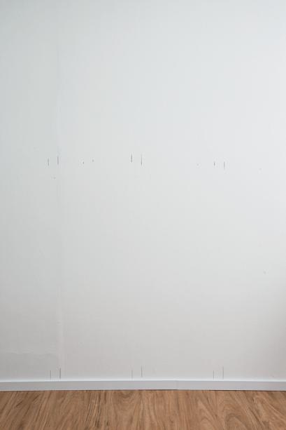 No papel, faça o projeto de acordo com a largura da parede que receberá a boiserie, calculando distâncias idênticas entre as peças. Transfira as medidas para a parede, iniciando pelas pontas. Risque a largura do perfil no topo e no rodapé (aqui tem 5 cm) e vá traçando até completar o desenho.
