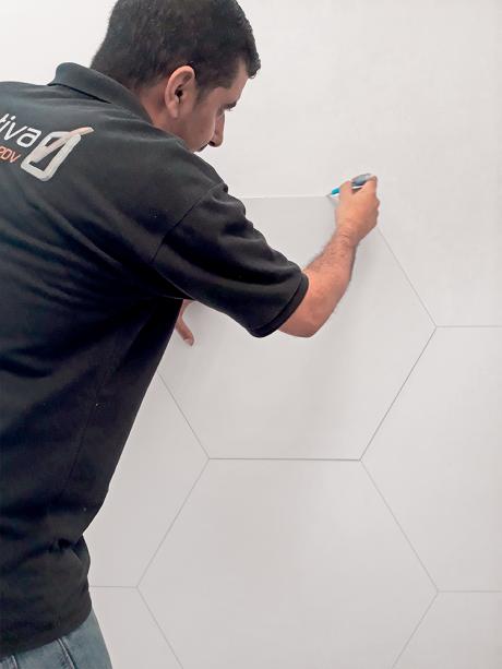 Em um papel encorpado, trace o hexágono e recorte-o. Use esse molde para riscar todas as peças na parede.