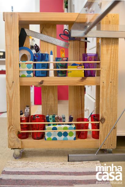 A peça fininha feita de paletes, foi disposta na vertical, ganhou rodízios, prateleiras e tiras cilíndricas fixadas com cola de madeira para evitar a queda dos objetos.