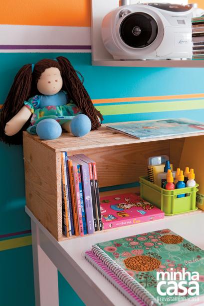 O caixote mantém os livros organizados na mesa de estudos.