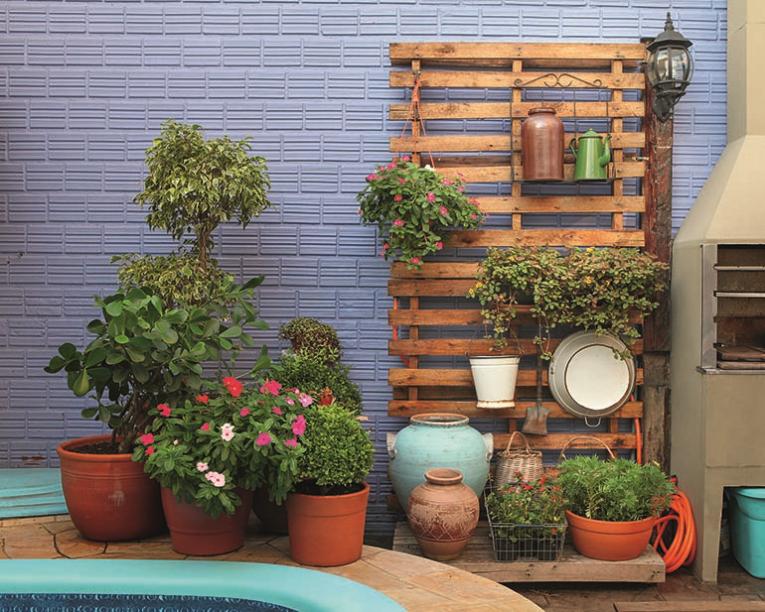 <span>Paletes medindo 1 x 1,20 m virou suporte para o jardim vertical. Vasos de barros em diferentes tamanhos acomodam as plantas.</span>