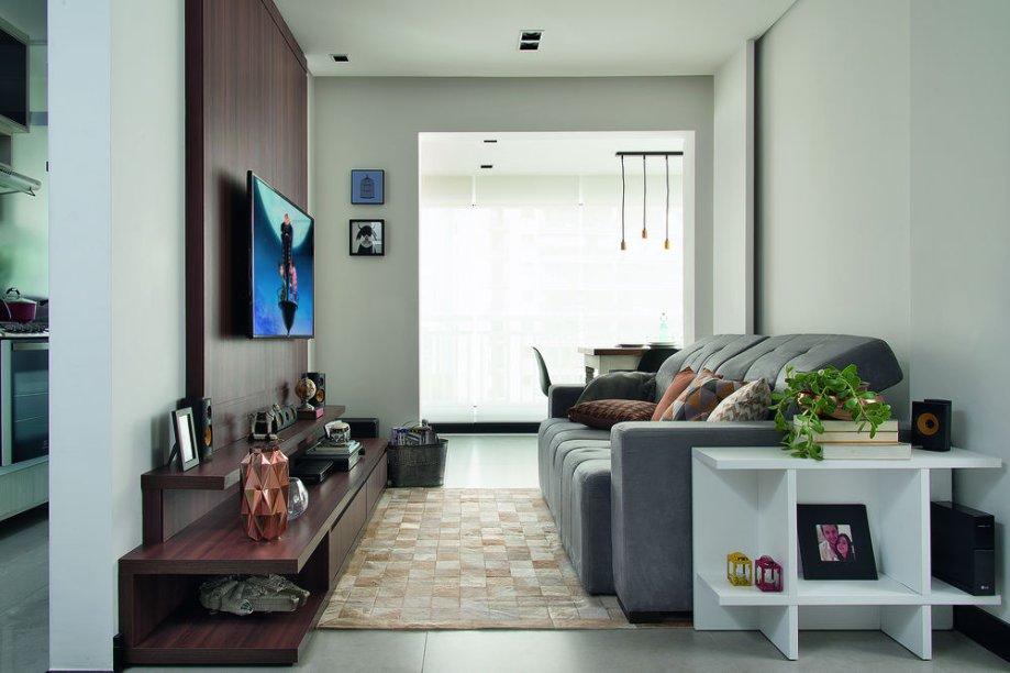 <span>Espaçosa, a sala de TV foi planejada com poucas peças, neutralidade e muita madeira. Os protagonistas são o rack com painel e o sofá de suede (Bulgari, 2,10 x 1,10 x 0,75 m*. Etna). Projeto do arquiteto André Bove, escritório Raduan Arquitetura.</span>